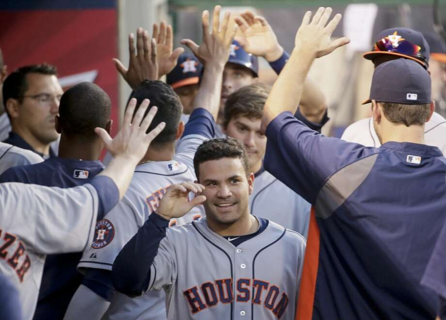 Jose Altuve celebrates in the dugout after scoring during the third inning Sunday.  Photo: Chris Carlson, Associated Press