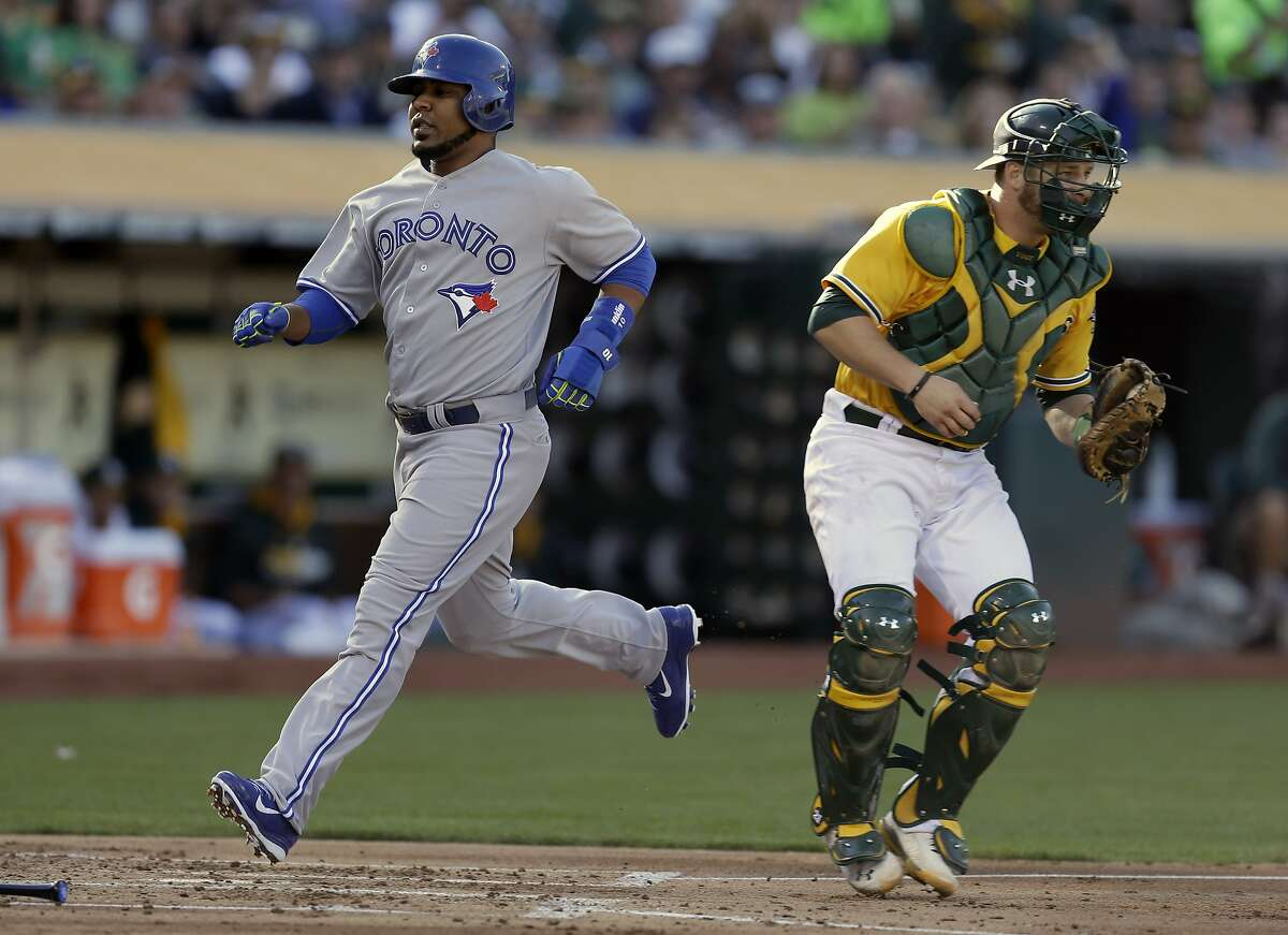 Toronto Blue Jays' Edwin Encarnacion, left, scores behind Oakland Athletics catcher Stephen Vogt in the first inning of a baseball game on Thursday, July 3, 2014, in Oakland, Calif. Encarnacion scored on a ground-out by Anthony Gose. (AP Photo/Ben Margot)