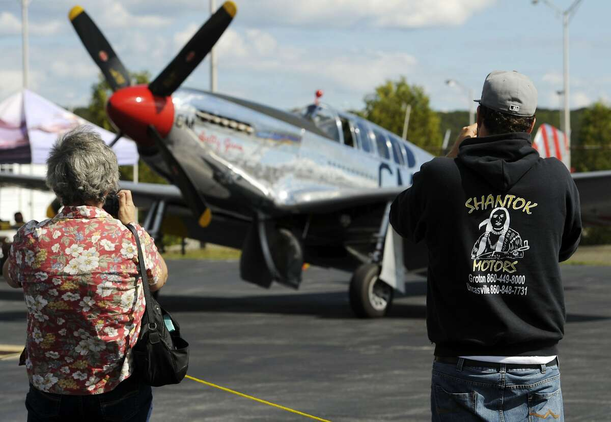 \Warbird enthusiasts snap photos of a Collings Foundation P-51C Mustang WWII fighter aircraft on display at Lanmar Aviation at Groton-New London Airport in Groton, Conn., Monday, Sept. 10, 2012. The three vintage WWII military aircraft; the P-51, a B-17G Flying Fortress and a B-24J Liberator , operated by the Stow, Massachusetts based Collings Foundation, will be open for tours 9 a.m. to 5 p.m. on Tuesday and 9 a.m. to noon on Wednesday. Admission is $12 for adults and $6 for children. WWII veterans may tour at no cost. Flight experiences in the B-17 and B-24 are $425 for a 30-minute flight. A 30-minute flight in the P-51 is $2200. (AP Photo/The Day, Sean D. Elliot)