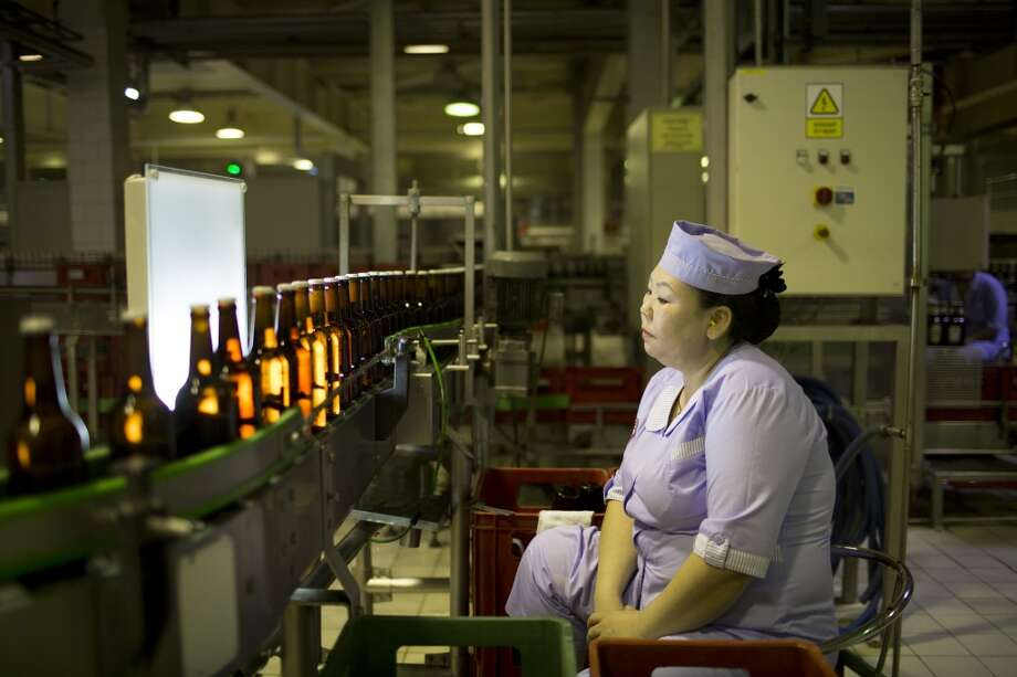 Mongolia: An employee inspects bottles of Niislel beer for defects at the APU JSC facility in Ulaanbaatar, Mongolia, on Tuesday, June 24, 2014. APU is Mongolia's largest spirit and beverage manufacturing company. Photographer: Brent Lewin/Bloomberg Photo: Brent Lewin, Bloomberg