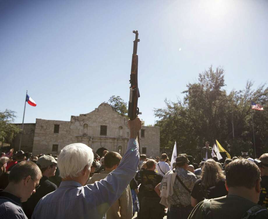A man raises his rifle during a pro-gun rally at the Alamo in 2013. A reader cautions against outlawing firearms. Photo: Michael Stravato / New York Times / NYTNS