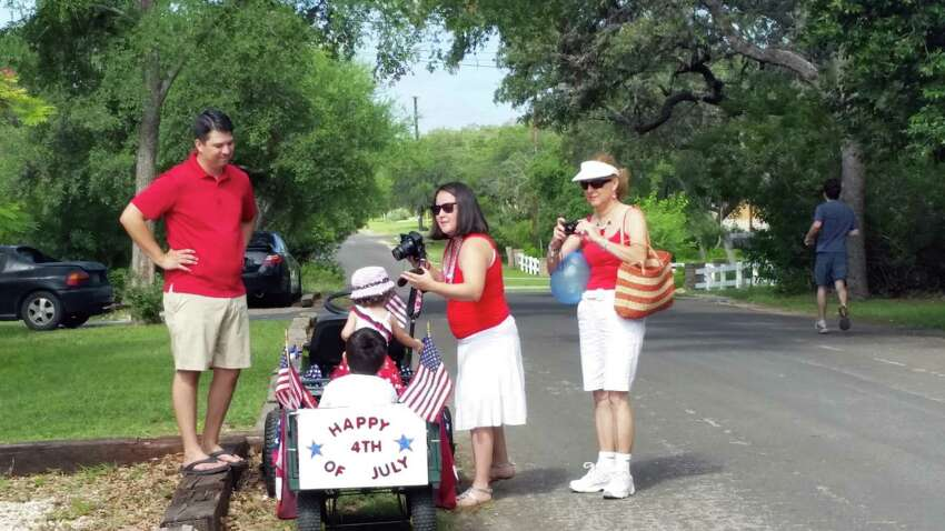 A family unloads children from their wagon at the conclusion of the Hills and Dales 4th of July parade on the West Side.