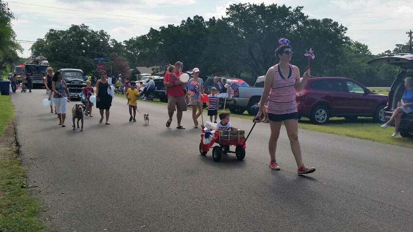 Erin Lunsford pulls her son, Riley Lundsford at the Hills and Dales 4th of July parade on the West Side of San Antonio. They were among about 200 people who walked about a half of a mile to the Charlie Bednarz Pavilion for free watermelon, hotdogs and other festivities.