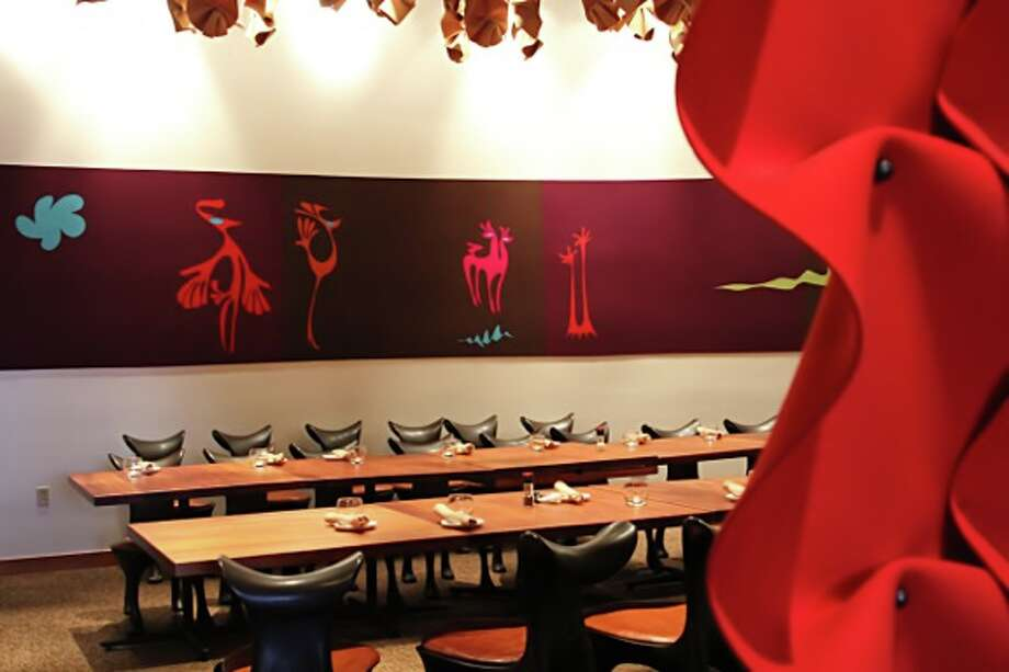 The group sat in Americas colorful private dining room. The wavy red curatin was drawn during the meeting.