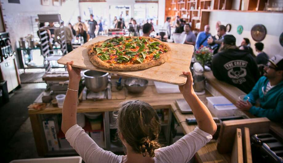 A pizza with basil leaves, cherry tomatoes and mozzarella is removed from the oven at The Mill cafe and bakery on Divisadero. Photo: John Storey, Special To The Chronicle