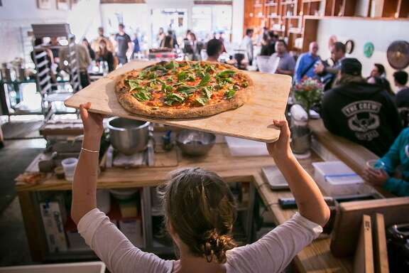 A pizza being taken from the oven during pizza night at Josey Baker Bread in San Francisco, Calif., on Monday, June 23rd, 2014.