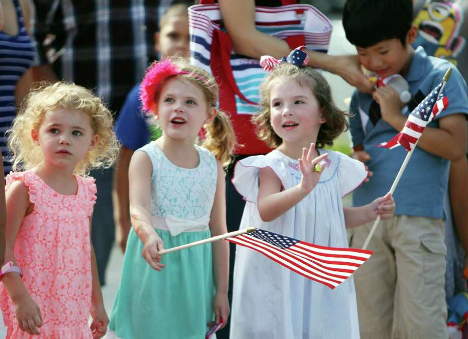 Sarah Garber, Juliette Garber, and Addie Yarbrough, wave during the Bellaire Fourth of July Parade where hundreds of people gathered to celebrate on July 4, 2014, in Houston, Tx. Photo: Mayra Beltran, Houston Chronicle / © 2014 Houston Chronicle
