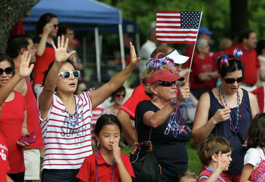 The crowd waves during the Bellaire Fourth of July Parade where hundreds of people gathered to celebrate on July 4, 2014, in Houston, Tx. Photo: Mayra Beltran, Houston Chronicle / © 2014 Houston Chronicle