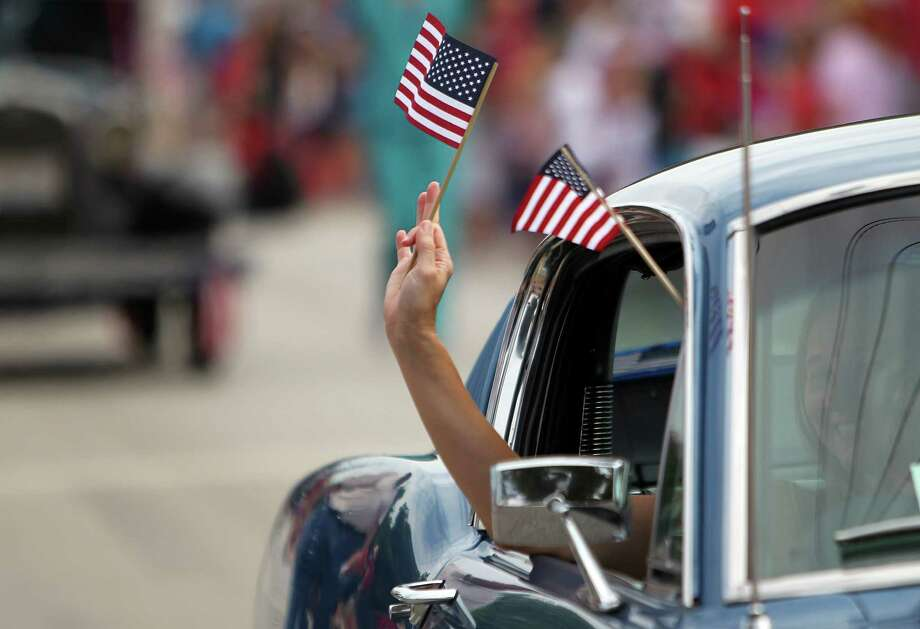 Participants wave US flags during the Bellaire Fourth of July Parade where hundreds of people gathered to celebrate on July 4, 2014, in Houston, Tx. Photo: Mayra Beltran, Houston Chronicle / © 2014 Houston Chronicle