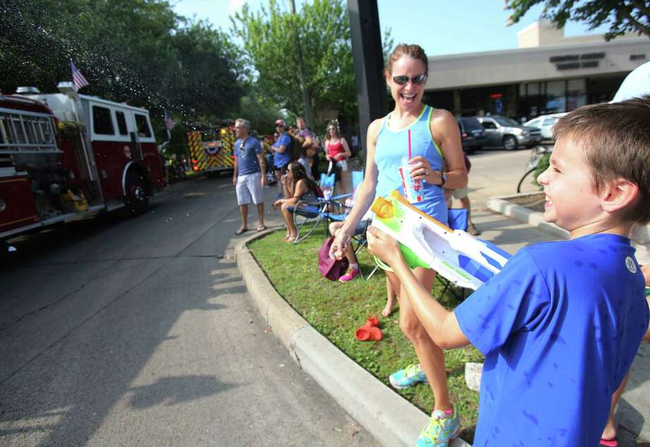 Jacob Dodson squeeze water to cool off fire fighters during the Bellaire Fourth of July Parade where hundreds of people gathered to celebrate on July 4, 2014, in Houston, Tx. Photo: Mayra Beltran, Houston Chronicle / © 2014 Houston Chronicle