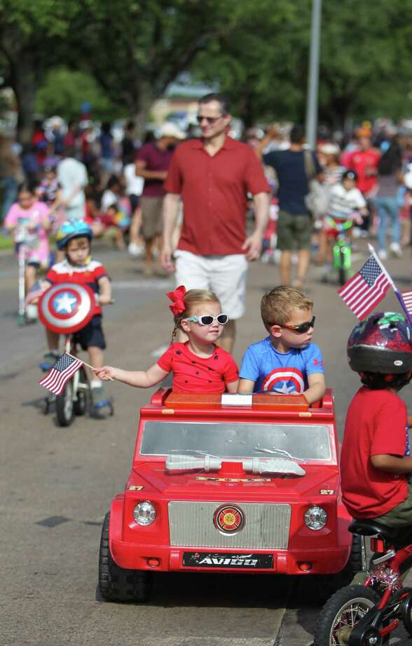 Lauren Herr, 3, and brother Hudson Herr, 4, join the Kids Parade which kicks off the Bellaire Fourth of July Parade where hundreds of people gathered to celebrate on July 4, 2014, in Houston, Tx. Photo: Mayra Beltran, Houston Chronicle / © 2014 Houston Chronicle