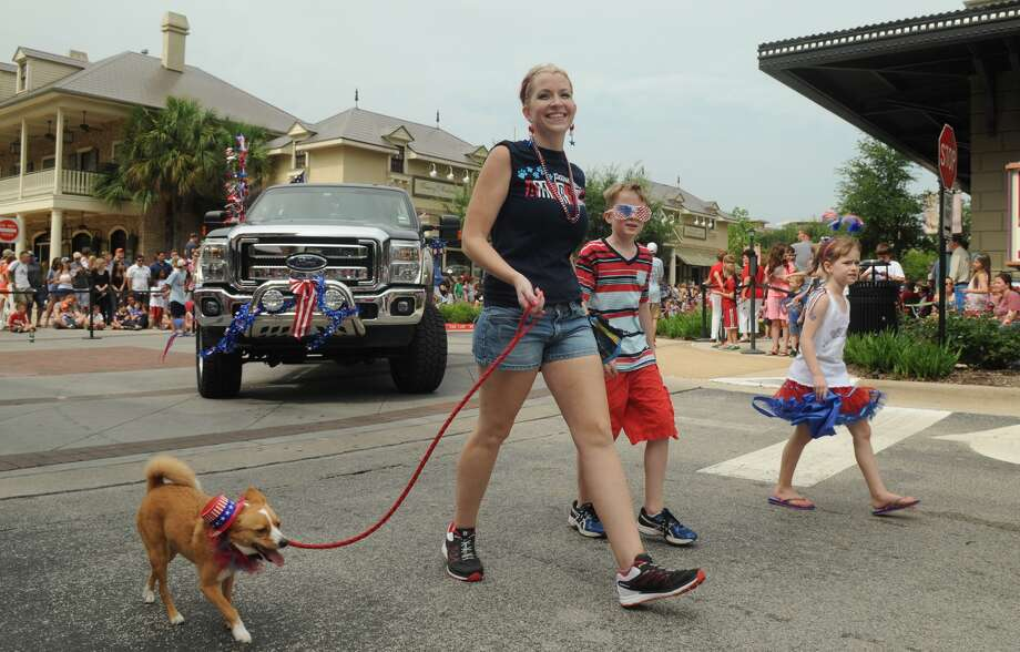 "Briony Scott, left, of The Brysis Pet Sitting in The Woodlands, and ""Brighton"", 3, walk the 39th Annual South Montgomery County 4th of July Parade in Market Street in The Woodlands on Friday. Photo: Jerry Baker, For The Chronicle"