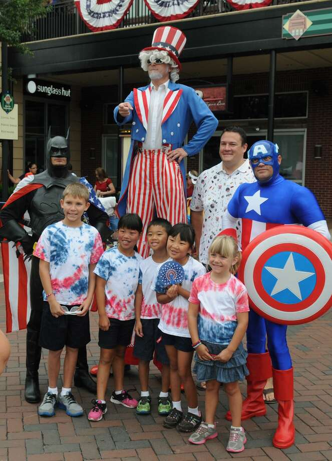 "Matt Ronsman, back row second from right, of The Woodlands, poses his children, including Luke, 10, front from left, Nora, 9, Drew, 7, Lily, 8, and Lauren , 5, for his wife, Ann Marie (not pictured), with ""Batman"", ""Uncle Sam"", and ""Captain America"" before the start of the 39th Annual South Montgomery County 4th of July Parade in Market Street in The Woodlands on Friday. Photo: Jerry Baker, For The Chronicle"