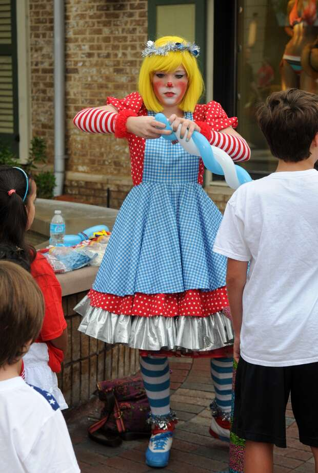 "Kimberly Schlosser, of Houston (77054), known as ""Watermelon the Clown"" and a member of AllHoustonClowns.com, works her balloon magic before the start of the 39th Annual South Montgomery County 4th of July Parade in Market Street in The Woodlands on Friday. Photo: Jerry Baker, For The Chronicle"