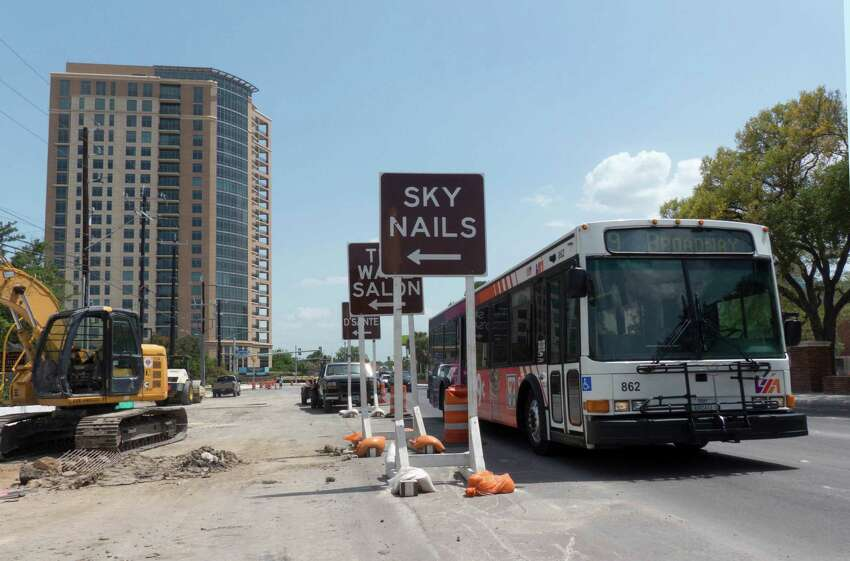 A bus drives by signs announcing entrances to businesses in the construction zone along Broadway near Hildebrand on July 3, 2014. The work on drainage and traffic flow improvements has been ongoing for more than one year. .