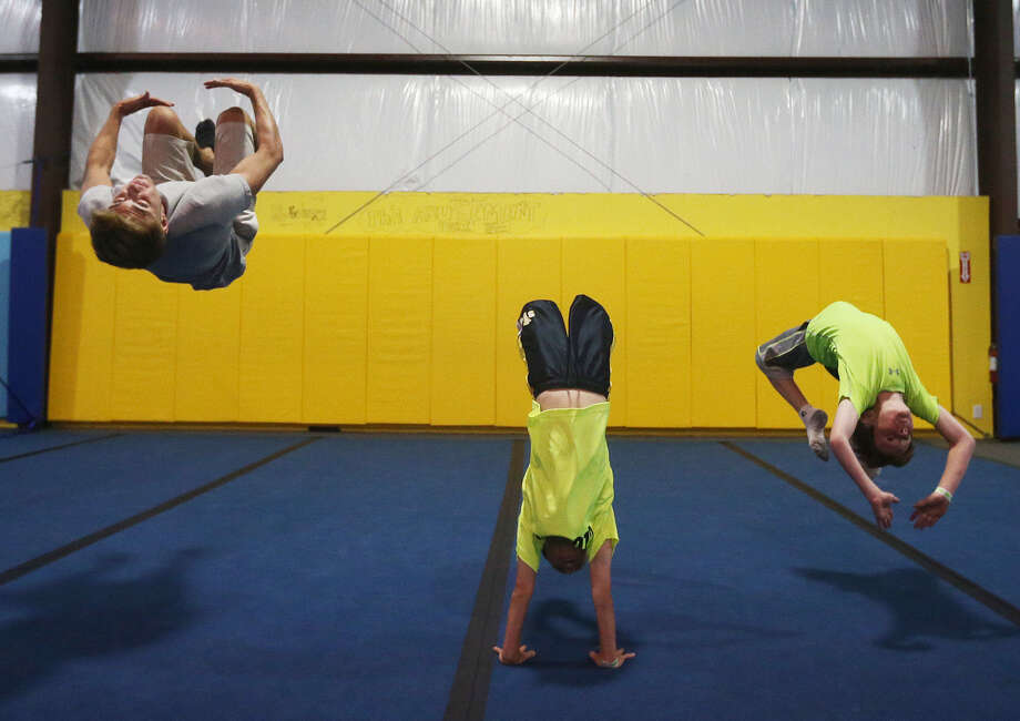 Forrest Hess, 19, Baur Sims, 8, and his brother, Luke Sims, 10, demonstrate flips at Spring Loaded Trampoline Park, just north of New Braunfels. Photo: Jerry Lara / San Antonio Express-News / © 2014 San Antonio Express-News