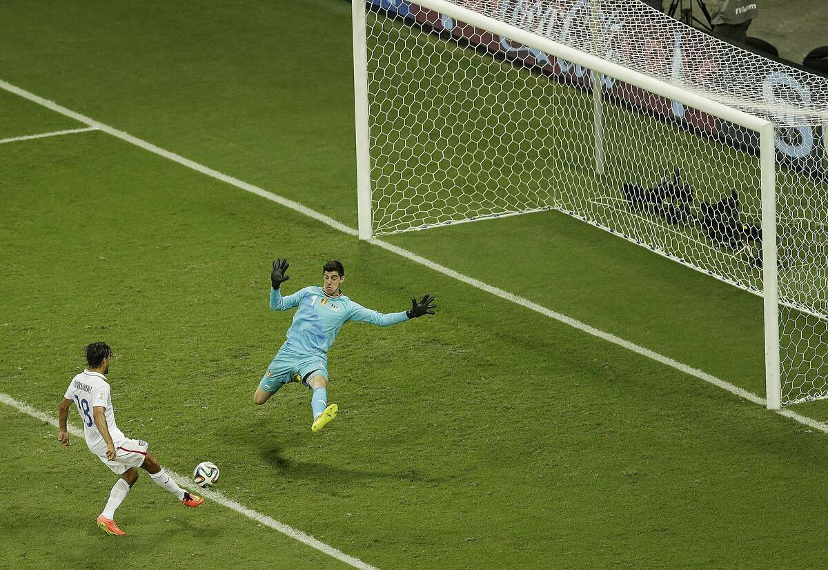 United States' Chris Wondolowski shoots past the goal of Belgium's goalkeeper Thibaut Courtois, right, during the World Cup round of 16 soccer match between Belgium and the USA at the Arena Fonte Nova in Salvador, Brazil, Tuesday, July 1, 2014. (AP Photo/Themba Hadebe)