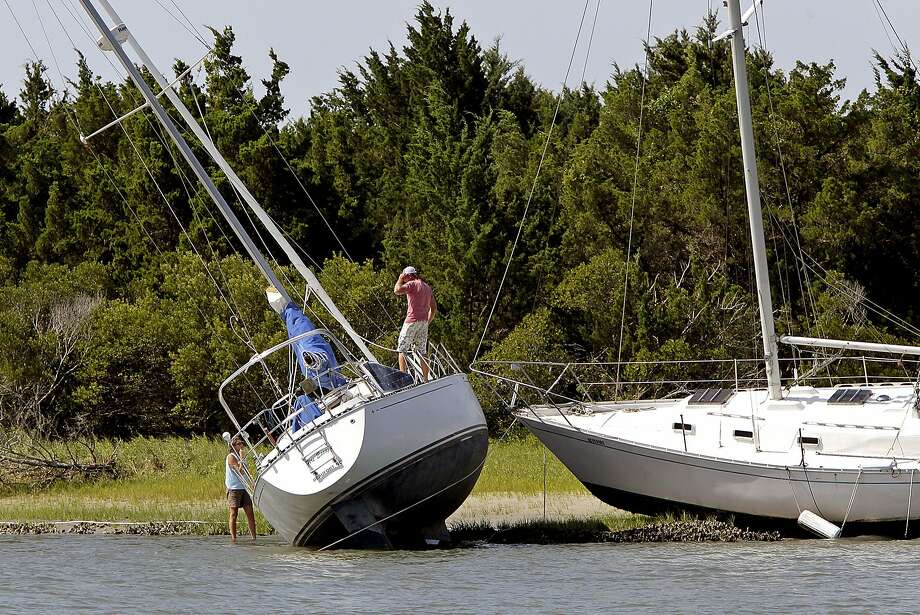 A boater ponders his predicament after his vessel was ripped loose by Hurricane Arthur and left beached on North Carolina's Carrot Island. Photo: Chris Seward, Associated Press