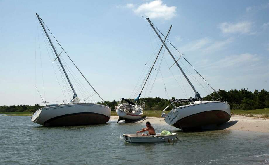 Jim Bonavito, of Beaufort, N.C., rows his dingy on Friday past sailboats that broke free of their moorings during the winds and waves from Hurricane Arthur, which took about five hours to cross the eastern part of the state. Photo: Randall Hill, FRE / FR170942 AP