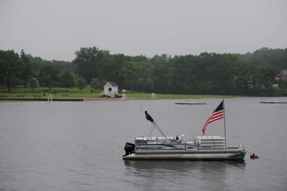 An American flag waves on a lone boat as rain falls upon Candlewood Lake near the vacant beach at Candlewood Park on Independence Day in Danbury, Conn. Friday, July 4, 2014. Photo: Tyler Sizemore / The News-Times
