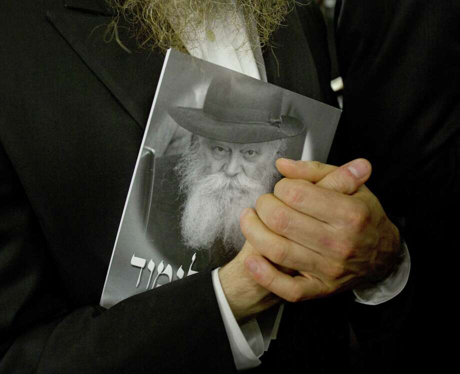 A man holds a publication showing Rabbi Menachem Mendel Schneerson, considered one of the most influential Jewish leaders of the last century, during a visit to his grave Monday. Photo: Victor J. Blue / New York Times / NYTNS
