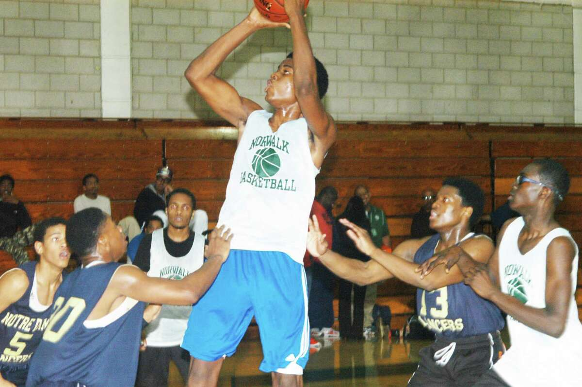 Norwalk's 6-foot-7 Steve Enoch shoots over a crowd of Notre Dame-Fairfield defenders during a pre-season scrimmage. Enoch and 6-foot-5 Roy Kane (far right) give the Bears good size in the frontcourt.