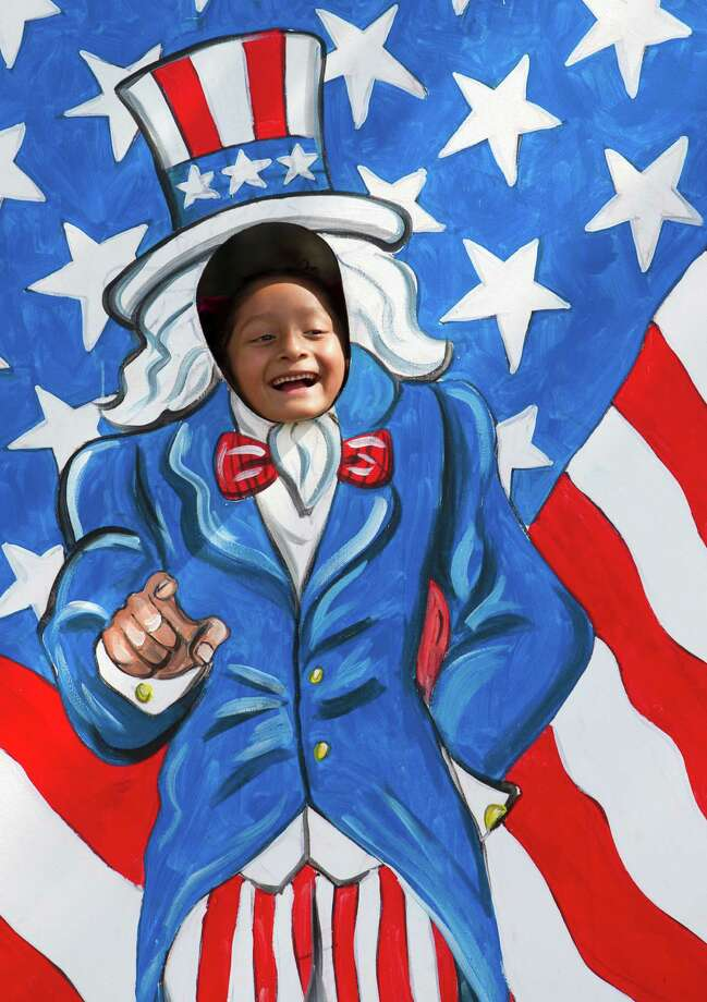 Alexandra Perez, 7, peeks through an Uncle Sam cutout during the Freedom Over Texas Fourth of July celebration at Eleanor Tinsley Park on Friday, July 4, 2014, in Houston. Photo: J. Patric Schneider, For The Chronicle / © 2014 Houston Chronicle