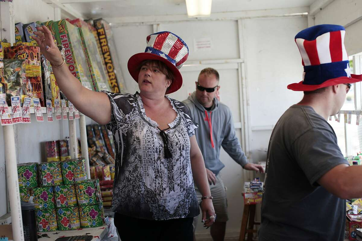 Marianne Lindblom, left, grabs fireworks for a customer at the Tanforan Shopping Center in San Bruno, Calif. on Thursday, June 3, 2014. San Bruno is only one of two Bay Area cities that sells fireworks for the 4th of July.