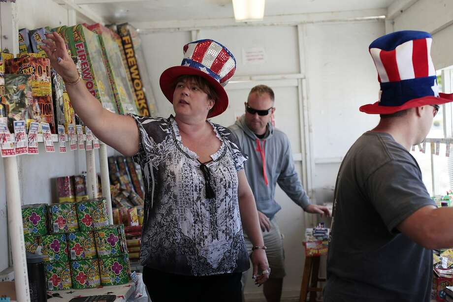 "Marianne Lindblom (left) grabs fireworks for a customer at the Tanforan shopping center in San Bruno, which is one of two San Mateo County communities that permits the sale of ""safe and sane"" fireworks. Photo: James Tensuan, The Chronicle"