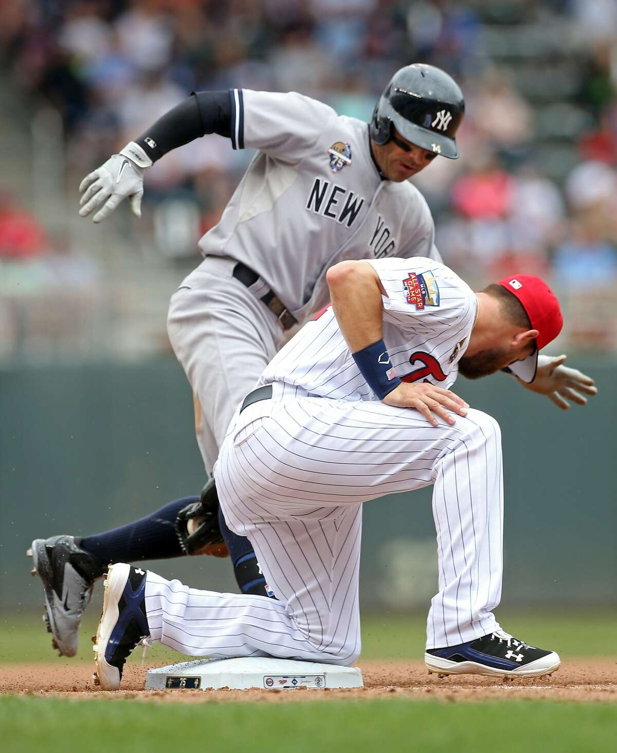 New York Yankees' Brian Roberts, right, beats the tag by Minnesota Twins' Trevor Plouffe to triple in the fourth inning of a baseball game, Friday, July 4, 2014, in Minneapolis. (AP Photo/Jim Mone)