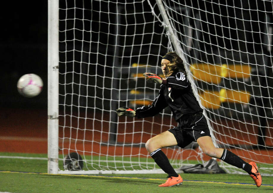 Danbury goalie Rebecca Gartner dives for the ball but doesn't come up with the save during a penalty kick at the Hatters' FCIAC semifinal game against St. Joseph's at Norwalk High School in Norwalk, Conn., on Monday, Oct. 28, 2013. Photo: Jason Rearick / Stamford Advocate