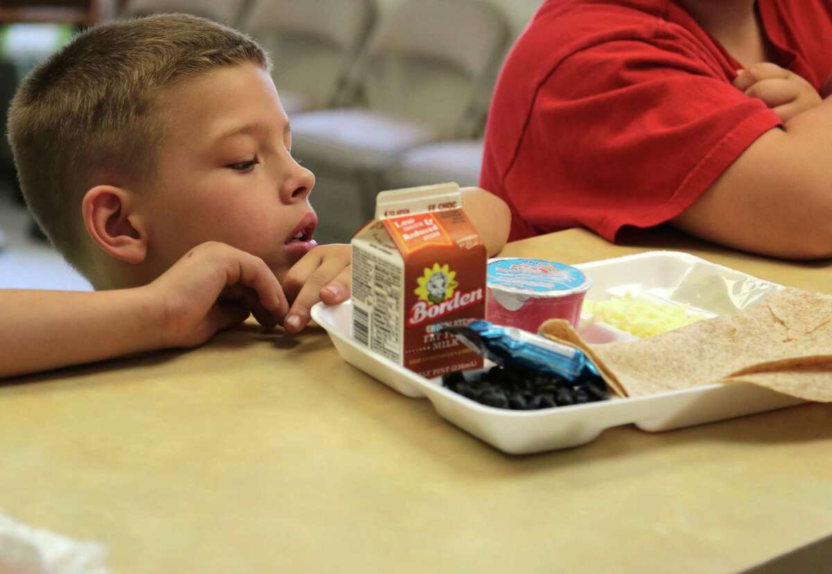 Eight year-old Carson Bone checks out his lunch Tuesday at a nonprofit in Patton Village, where his mom brings six kids for free meals provided by the Splendora school district.