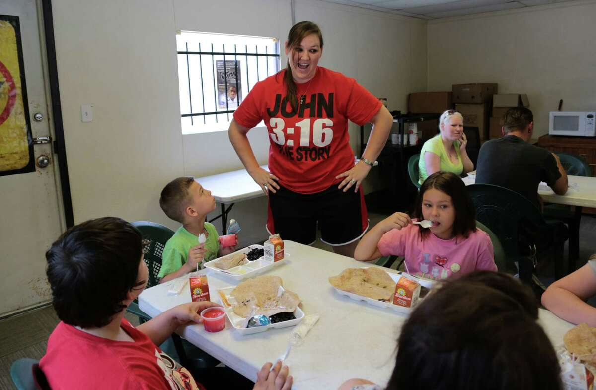 Volunteer Marleigh Clayton talks with the Willis family during lunch Tuesday at the newly opened nonprofit, Heaven's Army of Resources, in Patton Village.