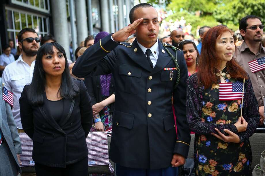 US Army solider Swaraj Pandey from Nepal salutes as the colors are presented during the 30th annual July 4th Naturalization Ceremony at Fisher Pavilion. Pandey was among 439 new US citizens who took the oath during the ceremony. He has been an active duty US Army solider for one year and is based and Joint Base Lewis McChord. Photographed on Friday, July 4, 2014. Photo: JOSHUA TRUJILLO, SEATTLEPI.COM
