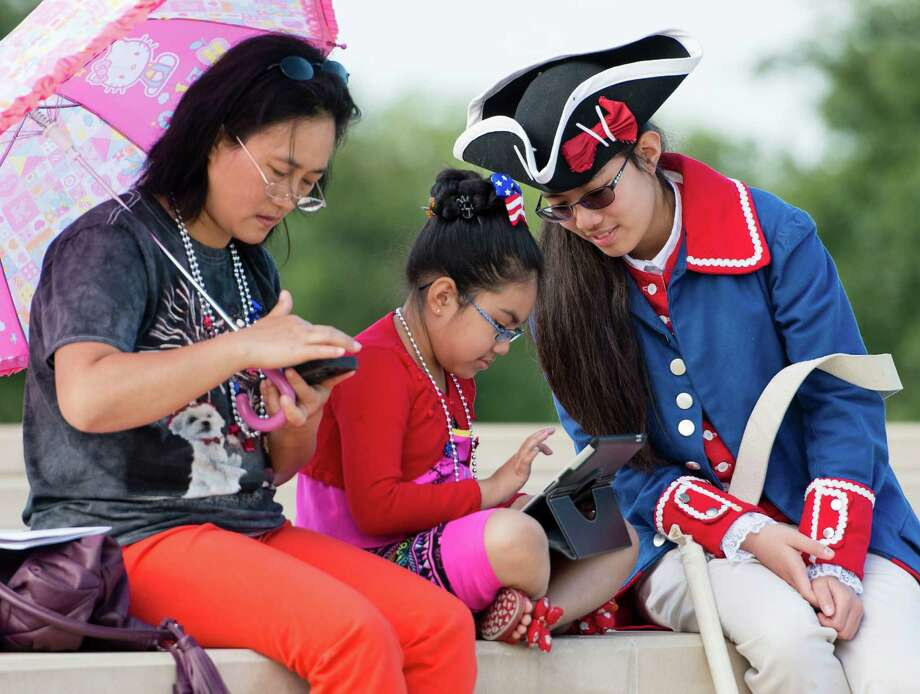 Fife player Miaoyin Rojas, 14, right, sits with her sister, Jackie Rojas, 6, and mother, Xiaoqin Rojas, left, before an Independence Day ceremony on Friday, July 4, 2014, at Fort Sam Houston National Cemetery in San Antonio. (Darren Abate/For the Express-News) Photo: Darren Abate, Darren Abate/Express-News / DA Media, LLC