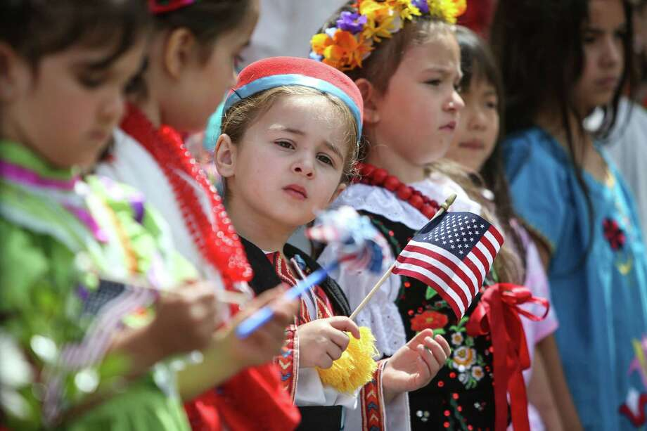 Children in traditional costumes take the stage during annual July 4th Naturalization Ceremony at Fisher Pavilion. Hundreds of new citizens will swear allegiance to a country that is deeply divided on its 241st birthday.  Photo: JOSHUA TRUJILLO, SEATTLEPI.COM / SEATTLEPI.COM