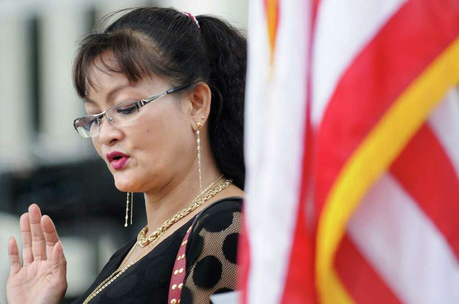 Rosi Giah Mason of Albany, a native of Vietnam, takes an oath of U.S. citizenship during a naturalization ceremony on Friday July 4, 2014, at the Empire State Plaza in Albany, N.Y. (Cindy Schultz / Times Union) Photo: Cindy Schultz / 00027120A