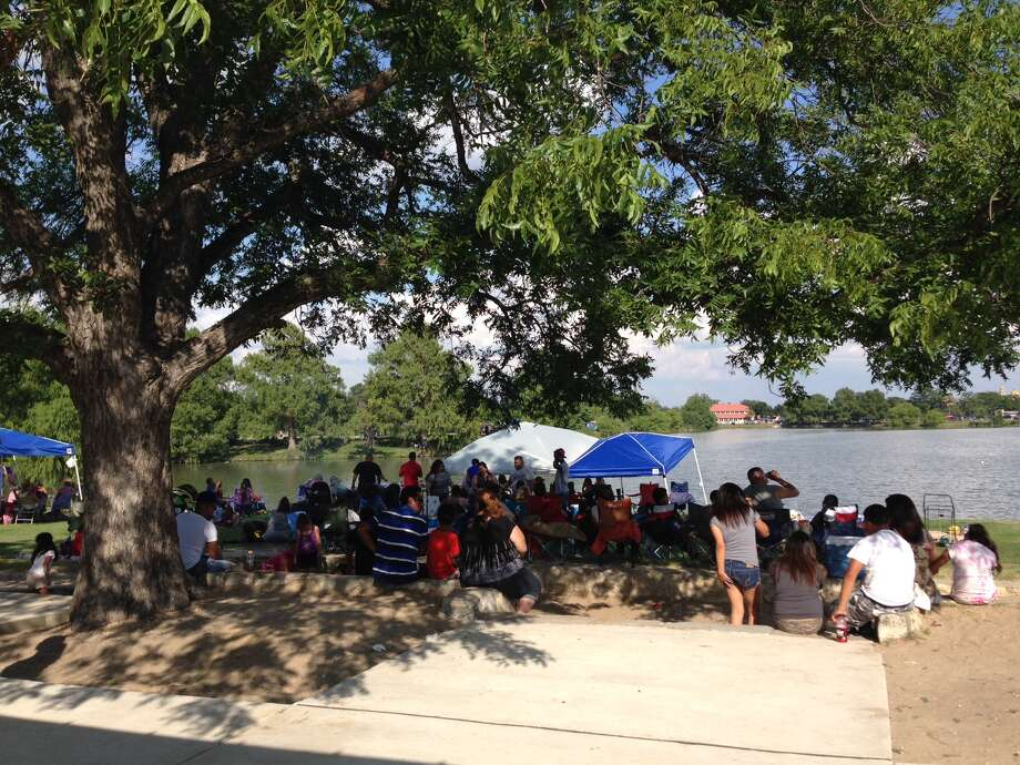 Families camp out under the shade of a tree waiting for fireworks on July 4, 2014. Photo: Katherine Schaeffer, Express-News