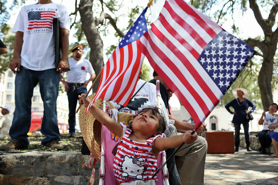 Alexis Torres, 1, entertains herself as speakers continue to address the crowd at Alamo Plaza after participating in the Immigration March to the Alamo on Friday, July 4, 2014. Photo: Lisa Krantz, By Lisa Krantz, Express-News / SAN ANTONIO EXPRESS-NEWS