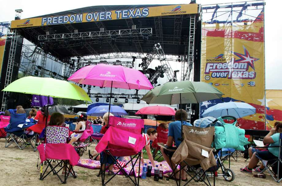 Festival goers take shelter under umbrellas as thunderstorms surround the area during the Freedom Over Texas Fourth of July celebration at Eleanor Tinsley Park on Friday, July 4, 2014, in Houston. Photo: J. Patric Schneider, For The Chronicle / © 2014 Houston Chronicle