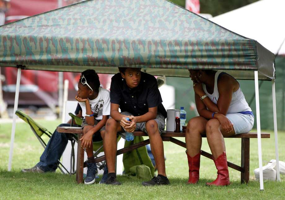 Collette Robertson takes shelter during lightning under a tent with her sons D'Angelo, 18, and D'Evayon, 9 during the 2014 Southwest Airlines Freedom over Texas at Eleanor Tinsley and Sam Houston Parks, Friday, July 4, 2014, in Houston. Photo: Karen Warren, Houston Chronicle / © 2014 Houston Chronicle