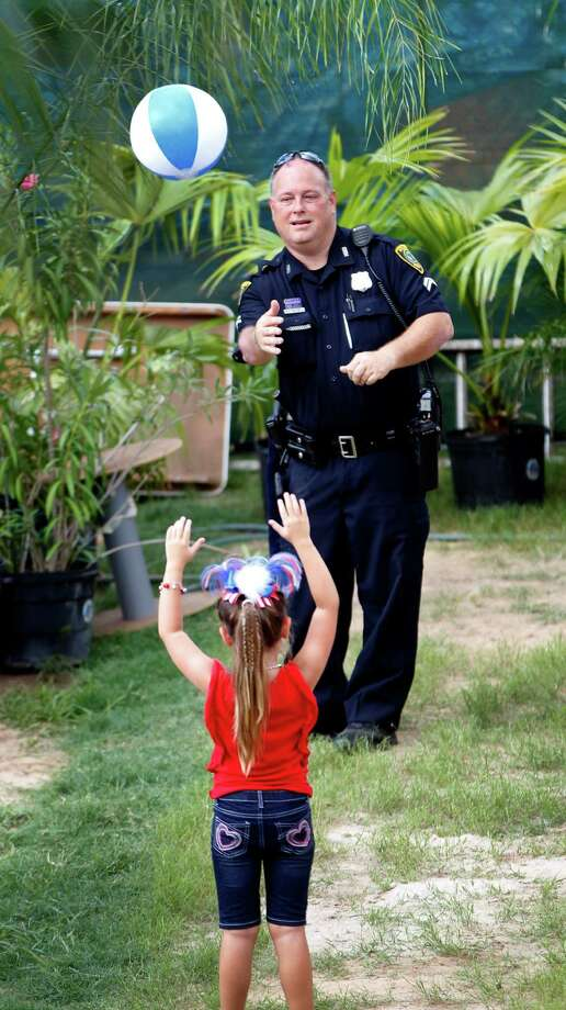 HPD officer Marte McDowell plays with a beach ball with Alexa Gray, 5, during the 2014 Southwest Airlines Freedom over Texas at Eleanor Tinsley and Sam Houston Parks, Friday, July 4, 2014, in Houston. Photo: Karen Warren, Houston Chronicle / © 2014 Houston Chronicle