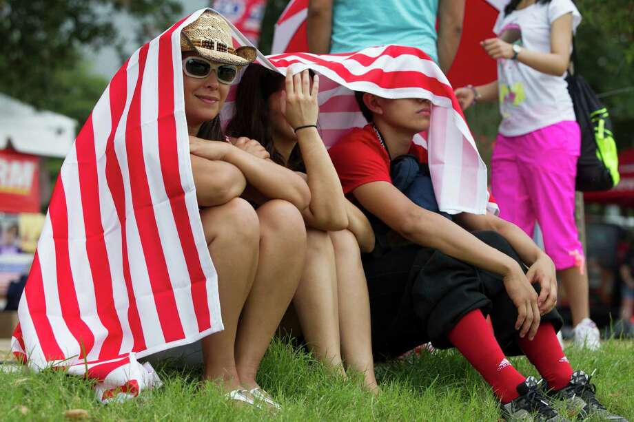 Festival goers take shelter under a blanket as thunderstorms surround the area during the Freedom Over Texas Fourth of July celebration at Eleanor Tinsley Park on Friday, July 4, 2014, in Houston. Photo: J. Patric Schneider, For The Chronicle / © 2014 Houston Chronicle