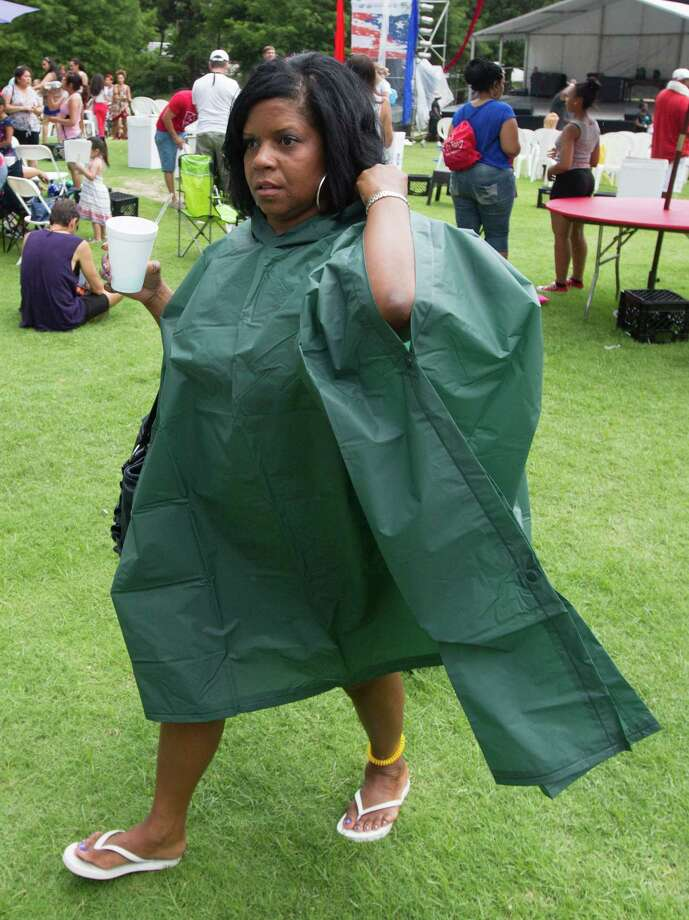 Joyce Bobo looks for shelter as thunderstorms surround the area during the Freedom Over Texas Fourth of July celebration at Eleanor Tinsley Park on Friday, July 4, 2014, in Houston. Photo: J. Patric Schneider, For The Chronicle / © 2014 Houston Chronicle