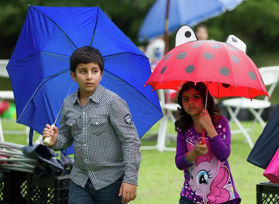 Young festival goers take shelter under umbrellas as thunderstorms surround the area during the Freedom Over Texas Fourth of July celebration at Eleanor Tinsley Park on Friday, July 4, 2014, in Houston. Photo: J. Patric Schneider, For The Chronicle / © 2014 Houston Chronicle