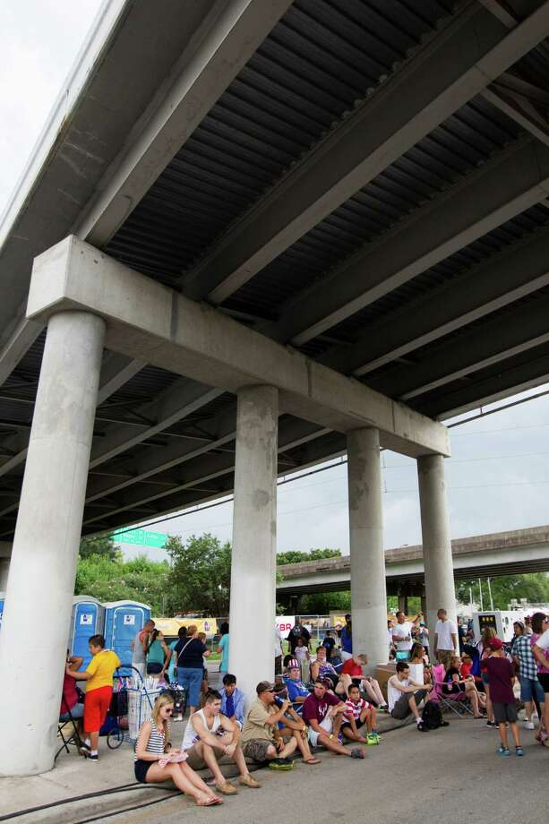 Festival goers take shelter under the I45 bridge as thunderstorms surround the area during the Freedom Over Texas Fourth of July celebration at Eleanor Tinsley Park on Friday, July 4, 2014, in Houston. Photo: J. Patric Schneider, For The Chronicle / © 2014 Houston Chronicle