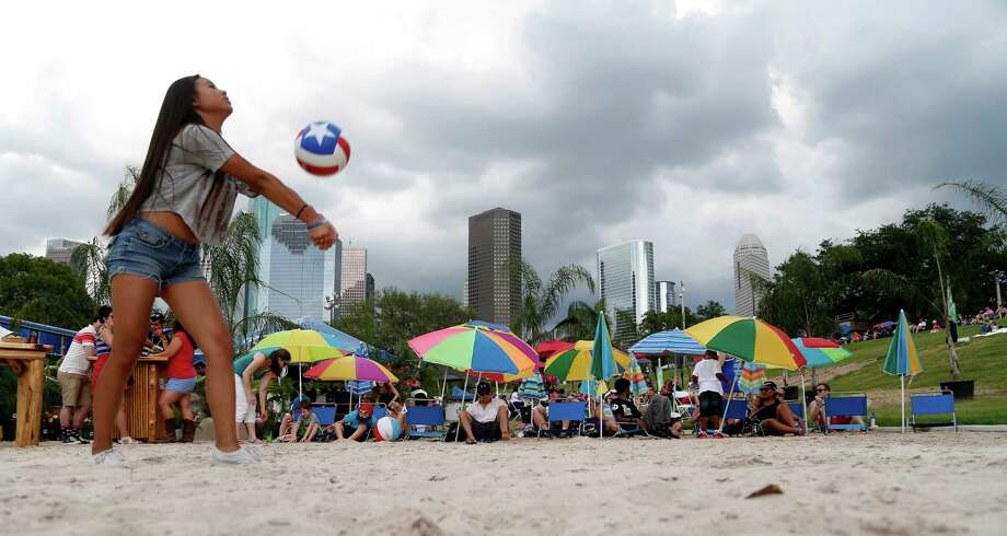 Hannah Mayfena plays volleyball with her aunt Karen May as the skies darken over downtown during the 2014 Southwest Airlines Freedom over Texas at Eleanor Tinsley and Sam Houston Parks, Friday, July 4, 2014, in Houston. Photo: Karen Warren, Houston Chronicle / © 2014 Houston Chronicle