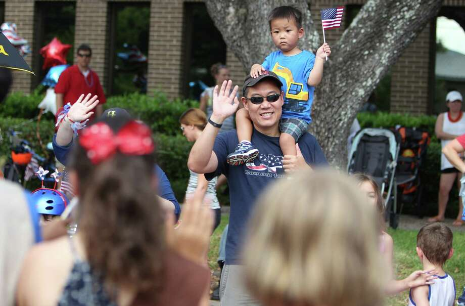 David Wu and son Maxwell Wu, 2, wave during the Bellaire Fourth of July Parade where hundreds of people gathered to celebrate on July 4, 2014, in Houston, Tx. Photo: Mayra Beltran, Houston Chronicle / © 2014 Houston Chronicle