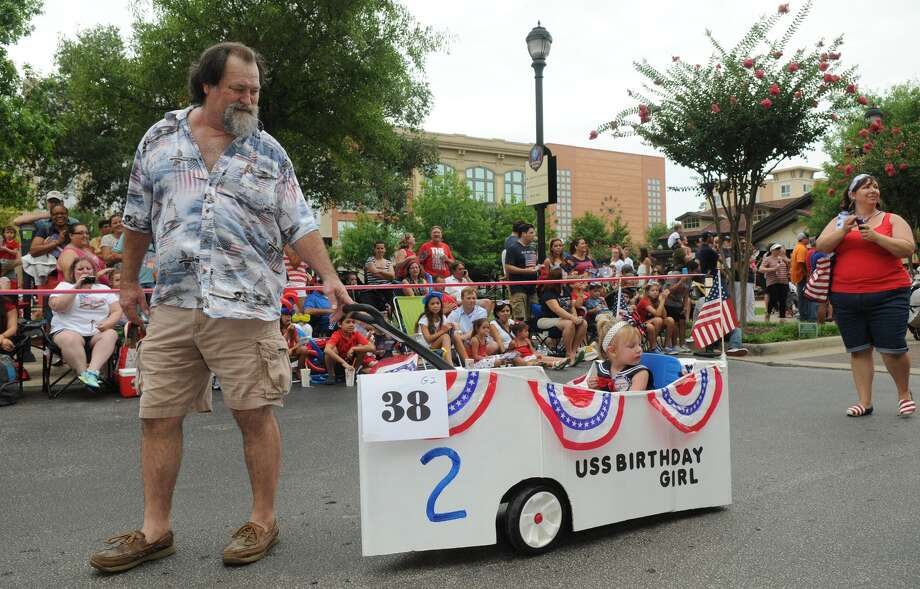 Mike Lybrand, from left, of Porter, pulls his granddaughter and 4th of July baby Ellie Klemm, 2, with her mom, Carolyn Klemm, of Addison but formerly of Humble, during the 39th Annual South Montgomery County 4th of July Parade in Market Street in The Woodlands on Friday. Photo: Jerry Baker, For The Chronicle
