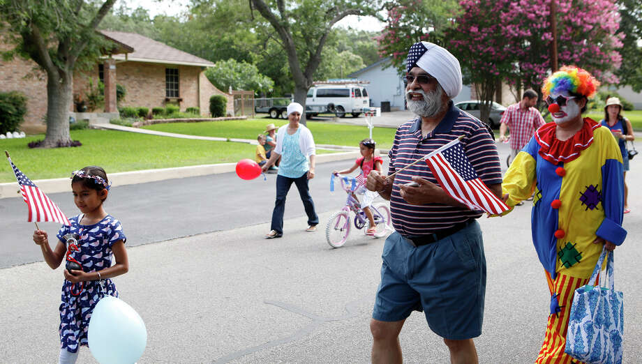 GP Singh (middle), his wife, Winkey, who dressed as a clown and other members of the Sikh Dharamsal congregation walk down Shady Hollow Lane as they participate for the first time July 4, 2014 in the 17th annual HIlls & Dales Neighborhood Association Fourth of July parade. The parade which lasted about a quarter of a mile had over 100 people participate while walking the two long block of Shady Hollow Lane off of Babcock Road. Photo: Cynthia Esparza, For The San Antonio Express-News / For the San Antonio Express-News
